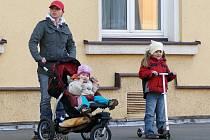 Rodinka na kolečkách: miminko v kočárku, dcerka na koloběžce a maminka dokonce na kolečkových bruslích vyrazili na jarní procházku.