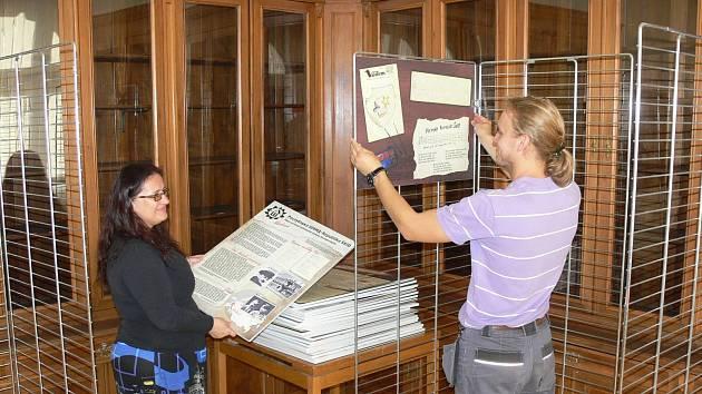 Ředitelka Regionálního muzea v Chrudimi připravuje zavěšení panelů výstavy.