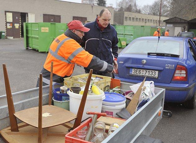 Zaměstnanec sběrného dvora vysvětluje řidiči auta, kam má uložit jednotlivé složky přivezeného odpadu.