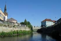 Jedna polovina řeky tekoucí městem od mostu u zimního stadionu a kolem sportovišť se proměňuje v městskou stoku směřující smutně do centra města k muzeu.