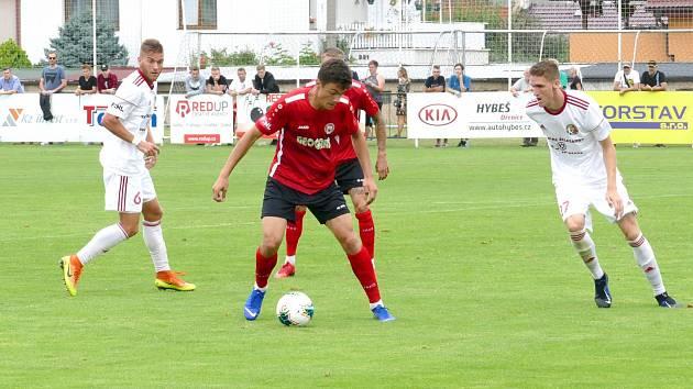 Vyrovnal. Petr Rybička (v červeném) druhou brankou v letošním sezoně zařídil Chrudim bod z horké třinecké půdy.