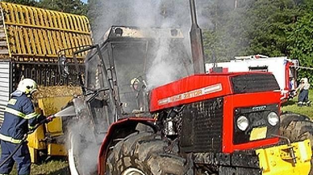 Hasiči likvidují požár traktoru.