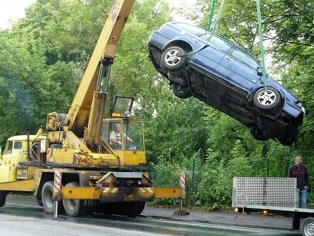 Odtahová služba vytahuje vůz ze stráně.