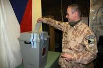 Voják českého provinčního rekonstrukčního týmu vhazuje obálku s hlasovacím lístkem do urny.