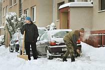 Muži i ženy makají na parkovišti před domem, aby si poradili s bílou záplavou. Opět ze slatiňanského sídliště.