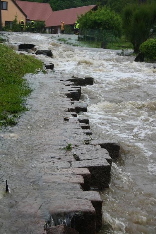 Ve Vápenném Podolu se přelil zdejší rybník, voda se vyvalila na sousední komunikaci, kterou vyrvala až na podloží včetně třiceticentimetrových dlažebních kostek, a udělala si ze silnice regulérní řeku. Potok vede vpravo podél silnice