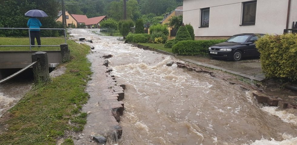 Ve Vápenném Podolu na Chrudimsku v neděli dopoledne dvě hodiny vydatně pršelo a výsledkem jsou zatopené ulice. Místní potok se vylil z koryta, voda vytrhala i dlažební kostky a razila si svoji cestu.
