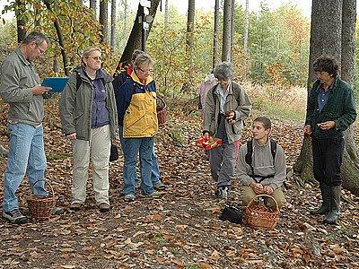 U rozcestníku nad výletní restaurací sleduje skupina výklad mladého mykologa Pavla Brůžka (klečí).