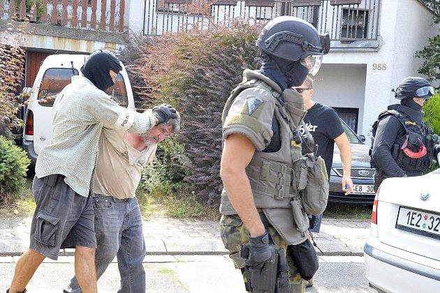 Příslušníci zásahové jednotky vyvádějí zadrženého muže