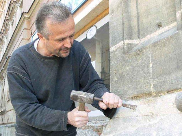 Restaurátor Ondřej Sigmund odstraňuje z fasády betonové záplaty.