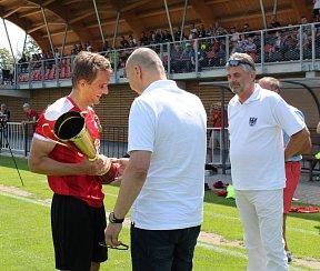 Kapitán MFK Chrudim Sebastien Langr přebírá pohár od člena výkonného výboru FAČR Michala Blaschkeho, přihlíží starosta Chrudimi Petr Řezníček.