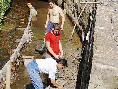Dělníci opravují opěrnou zeď mostku.
