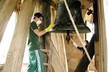 Mart-Džan z Ankary čistí zvon ve věži kostela sv. Matouše na Hradíšťku, za ním Míša z Čech ometá pavučiny z trámů.