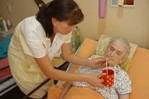 Pracovnice sociální péče Eva Novotná podává pití v hořickém domově důchodců Marii Adamcové.
