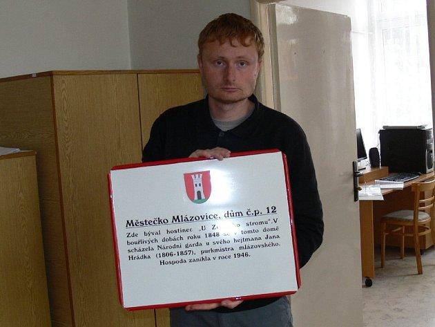 Mlázovický starosta Tomáš Komárek s jednou z informačních cedulí.