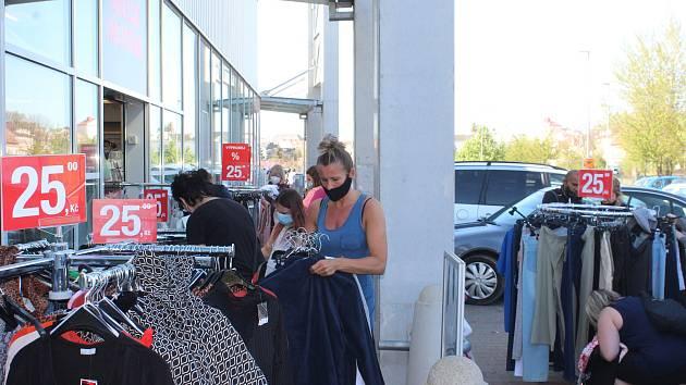Parkoviště v obchodní zóně bylo v pondělí plné, Lidé se srocoali předeším před obchdy s oblečením.