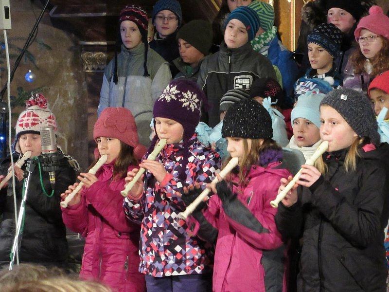 Koncert lužanských dětí s pedagogy ve vyzdobeném kostele.