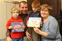 Ondra Dušek s rodiči a bráškou převzal v naší redakci víčka a drobné dárky.