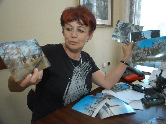 Ředitelka hořické knihovny Ilona Hynková s fotografiemi přijatými do fotosoutěže.