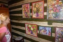 Galerie plná chaloupek a květin.