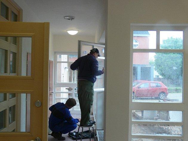 Řemeslníci dokončují poslední úpravy v areálu pečovatelské služby.