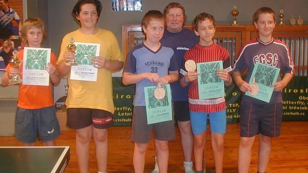 Úspěšní mladí žáci turnaje ve stolním tenise na společném snímku s Milanem Ročkem.