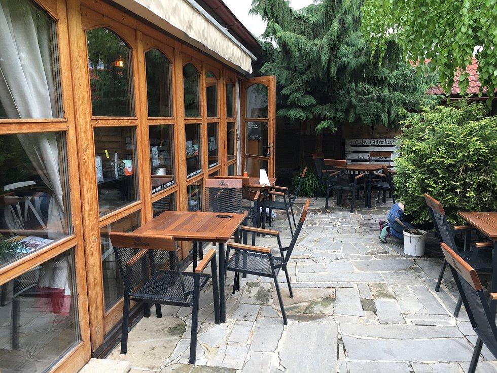 Zahrádka Café Všehochuť je příhodně schovaná a vysokou kamennou zdí přímo u Valdštejnova náměstí.