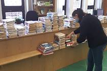 Od pondělí si už mohou čtenáři jičínské knihovny opět vypůjčovat knižní tituly, i když zatím jen omezeně přes výdejní okénko. Knihovnice od rána zpracovávají objednávky a průběžně připravují hromádky. Foto: knihovna Jičín