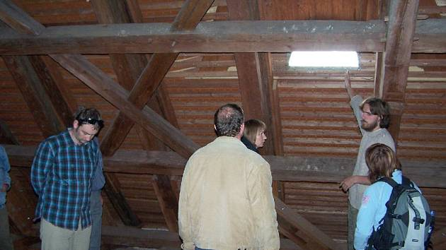David Číp z Českého svazu ochránců přírody předvádí v krovu kostela možnost instalace budky pro kavky na okénko objektu.