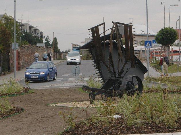 Kruhový objezd u autobusového nádraží zdobený zemědělským strojem.