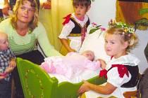 Vítání nových občánků ve Třtěnici bývá také doprovázeno vystoupeními dívek ze souborečku Sedmikrásky. Na snímku maminka Miluška Myšková se synkem Marečkem, dcerkou Karolínkou a druhou dcerkou Terezkou ve starodávné  dřevěné kolébce.