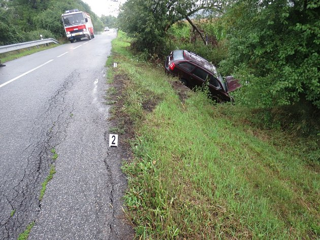 Mladá řidička dostala na mokré silnici smyk, auto museli na silnici vrátit hasiči.