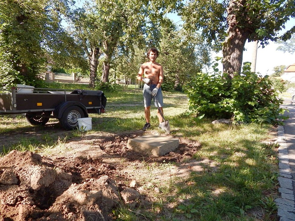 Kameník Martin Šafka upravuje terén kolem kamenných dlaždic.