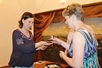 STAROSTKA  městečka Pecka Hana Štěrbová předává pokřtěnou stříbrnou minci kastelánce peckovského hradu Věře Kociánové.
