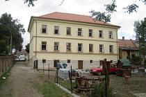 NA KONCI září bylo vzdělávací centrum těsně před dokončením. Dělníci provádí finální úpravu dětského hřiště.