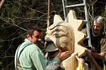 Autor upevňuje dřevěnou  plastiku na totem.