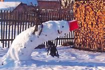 Dvoumetrový sněhulák po dnu slunečního svitu.