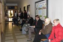 Lidé čekající na výplatu sociálních dávek.