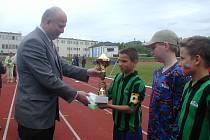 Starosta Martin Puš předává pohár Danielu Komárkovi.