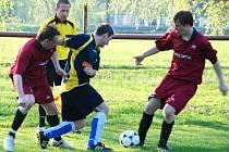 Vladimír Kalenda a Lukáš Novotný (v červeném) bojují o míč s obráncem hostí.