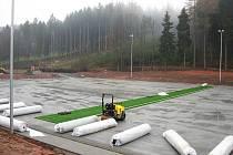 Z pokrývání povrchu nového hřiště.
