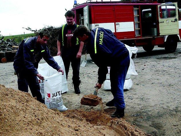 Miletínští hasiči rozdělují protipovodňové pytle.