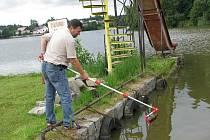 Josef Tlustý u pávovského rybníka předvádí, jak se odebírají vzorky pro laboratorní analýzu mikrobů.