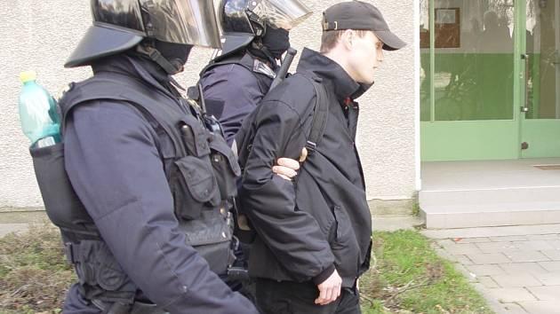 Těžkooděnci odvádějí do policejního auta zatčeného neonacistu Jiřího Švehlíka.