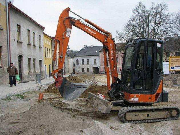 Polenské Karlovo náměstí prochází po desetiletích klidu velkými stavebními úpravami. Po inženýrských sítích se dokončují povrchy. Pod ramenem malého bagru je vzadu vidět rabínský dům a část židovské synagogy.