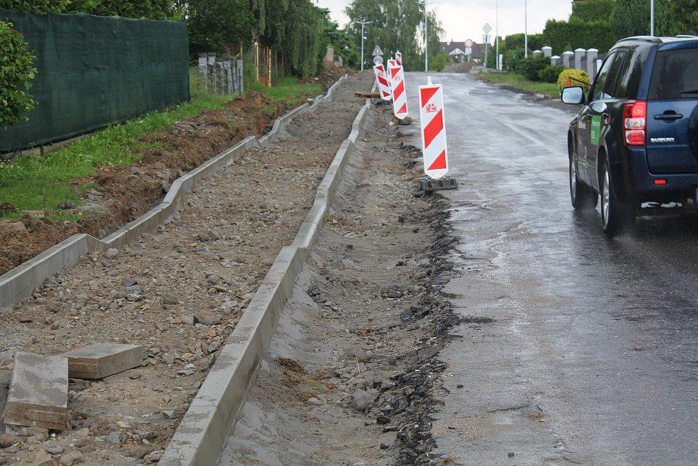 Obrubník byl původně až u asfaltu, dělníci ho museli posunout.