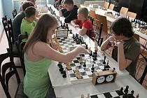 Děvčata a chlapci usedli nad šachovnicemi..