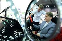 Ve zpětném zrcátku. Za volantem sedí v saku jeden ze stavitelů auta, student David Němec. Nad ním stojí jeho kolega z týmu Josef Hoskovec. Auto bude do neděle k vidění v City Parku.