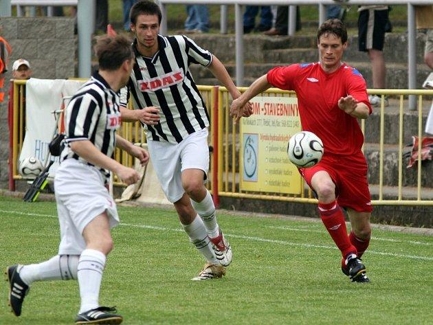 Derby Třebíče se Žďárem nabídlo zejména v závěru zajímavý fotbal. Nakonec si oba celky připsaly po bodu. Na snímku se třebíčský stoper Michal Vejmelka (v červeném) snaží uniknout žďárskému útočníkovi Pavlu Smetanovi.