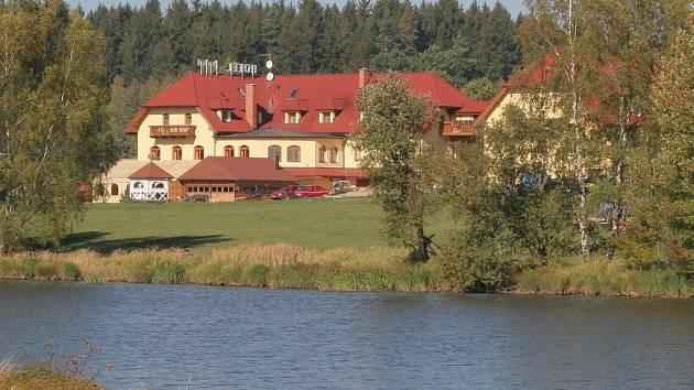 Rybáři Písařský rybník využívají k zimnímu komorování ryb.  Za ním stojí hotel Tři věžičky.